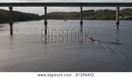 Orange Dinghy Approaching Bridge
