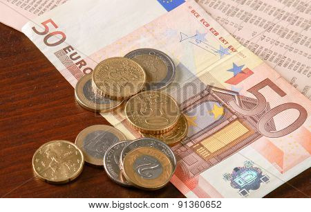 Money: euro coins and bills close up isolated on wood background