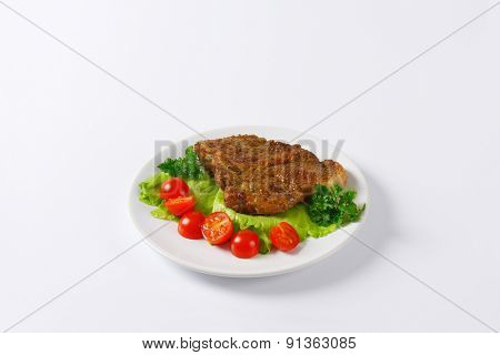 slice of roasted pork meat with vegetable garnish on white plate