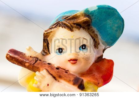 macro photography depicting a small statue of a young boy playing flute