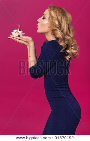 Beautiful Blonde Woman In Luxury Blue Dress And Curly Hairstyle Blowing Candle On Birthday Cake. Cle