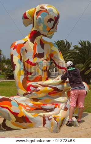 Woman working painting colourful statue