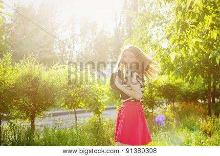 Lovely Girl With Flying Hair Holds Hat In Her Hands