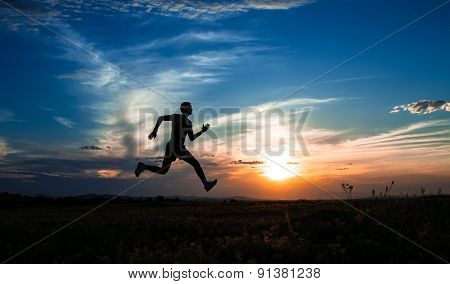 Silhouette Man Running And Jumping, On Meadow, Sunrise -sundown Sky At Background. Runner - Sprinter