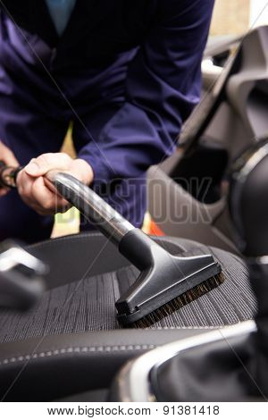 Man Hoovering Seat Of Car During Car Cleaning