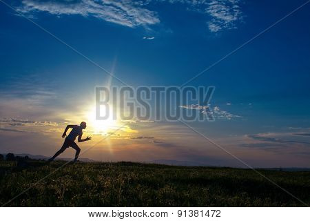 Silhouette Man Running On Meadow, Sunrise -sundown Sky At Background. Runner - Sprinter On Field