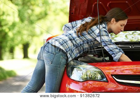 Broken Down Female Driver Looking Under Hood Of Car