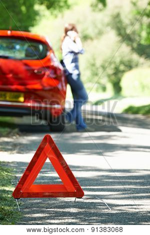 Female Driver Broken Down On Country Road With Warning Sign In F