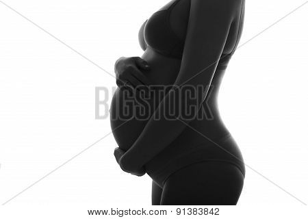 Pregnan Woman In Underwear Cherish Her Belly. Silhouette Black And White Photo. Isolated