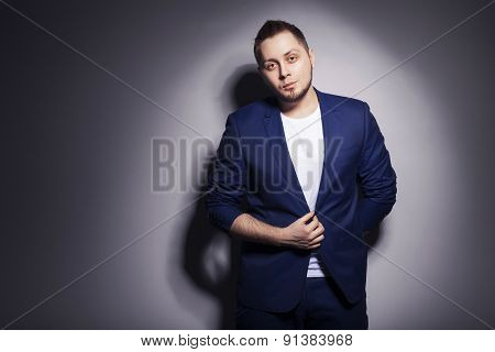 Stylish handsome man in blue casual buisness suit standing near a wall