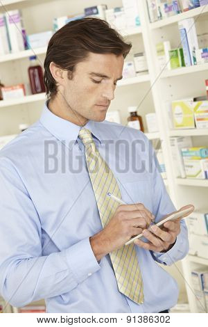 UK pharmacist in pharmacy with prescription