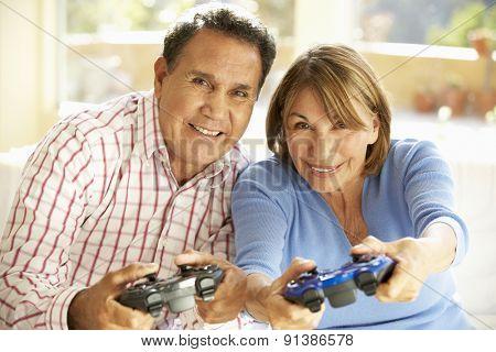 Senior Hispanic Couple Playing Video Game At Home