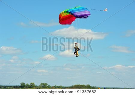 Tandem parachute against clear blue sky