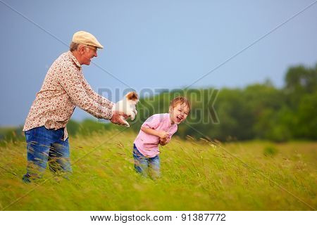 Happy Grandfather With Grandson Having Fun On Summer Field