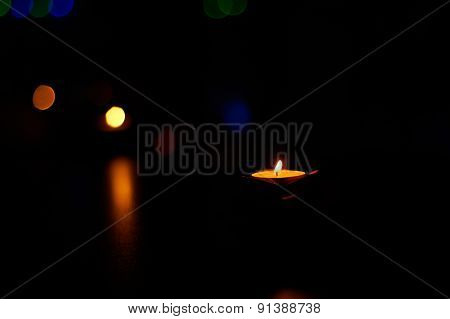 Burning candles on the dark wooden table