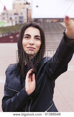 Beautiful Brunette Woman On A Walk In European City Using Her Smartphone Making Selfie. Outdoors
