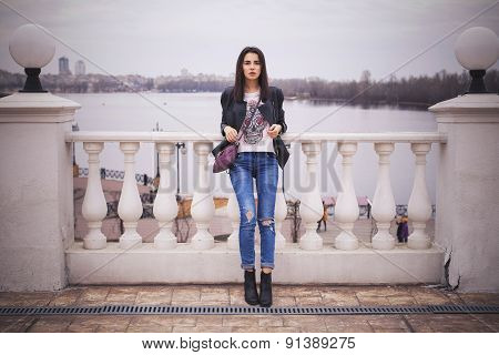 Beautiful Brunette Woman In Black Leather Jacket Walking On The European City Street