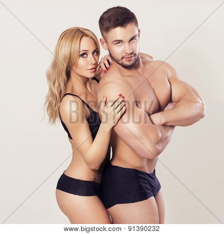 Sexy Fit Muscled Couple In Sportswear On Neutral Grey Background Hugging
