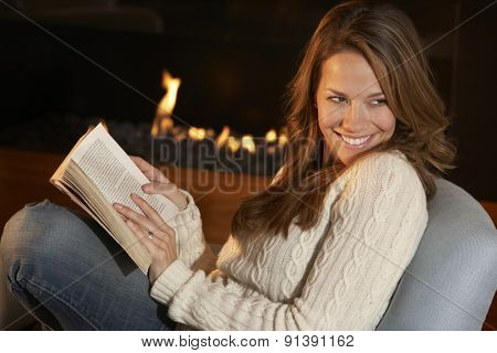 Woman reading in front of fire at home