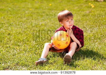 Little boy sitting on grass with ball