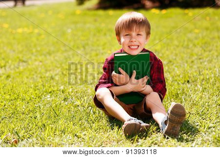 Smiling boy sitting on grass and hugging book