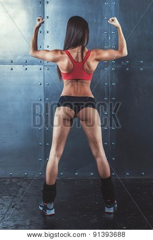 Muscular active athletic young woman showing muscles of the back shoulders and hands fitness, sport,