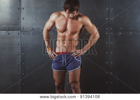 Portrait of fit athletic muscular shirtless young man looking down Fitness sport training fitness he