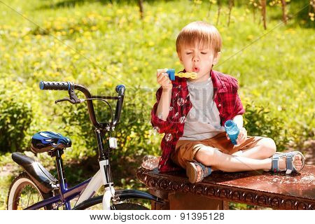 Little boy in park blowing bubbles