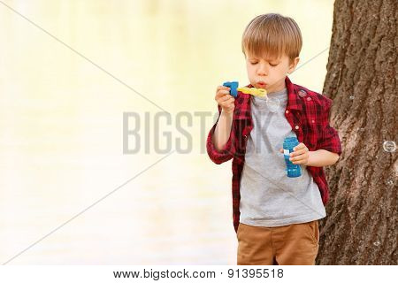 Little boy blowing bubbles in front of tree