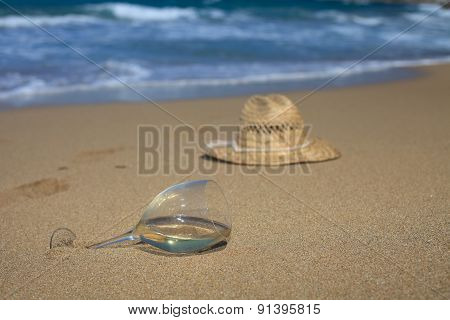 A Glass Of Wine And A Hat In The Sand On The Seashore