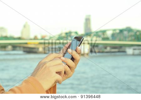 Male Hand Using Mobile Smart Phone Near The Iron Bridge In Bangkok As Wireless Device Technology Con