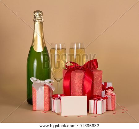 Bottle and wine glasses with gifts