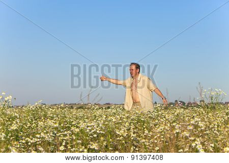 The happy young man in the field with a bouquet of camomiles