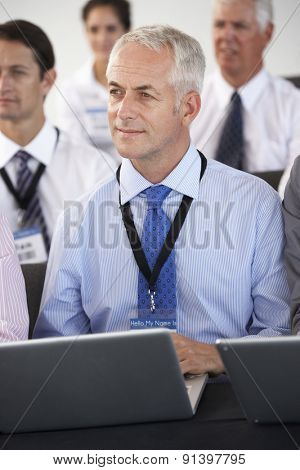 Male Delegate Listening To Presentation At Conference Making Notes On Laptop