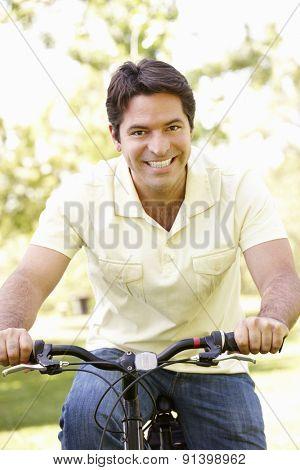 Young Hispanic Man Cycling In Park