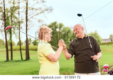 Senior man and woman holding hands together