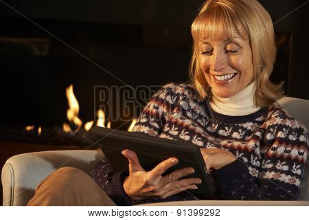 Mature woman using tablet in front of fire at home