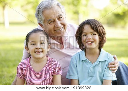 Hispanic Grandmother And Grandfather Relaxing With Grandson In Park