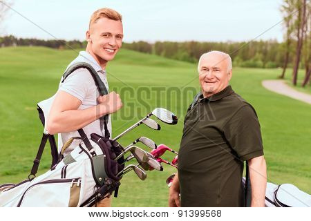 Senior and young golf players with equipment