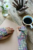 stock photo of sad christmas  - Women hand wear wool gloves in wintertime writting letter for lover from distant lonely background in cold day of christmas season hot coffee cup flower pot pencil on wooden background - JPG