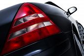 stock photo of low-light  - Close up low angle view of the red rear tail light assembly on a modern black car showing lens detail isolated on white - JPG