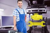 stock photo of auto repair shop  - Smiling young male repairman carrying toolbox against auto repair shop - JPG