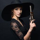 image of pirate girl  - girl pirate with ancient pistol in hand on a black background - JPG
