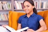 picture of toothless smile  - Beautiful African female student reading a book and smiling while sitting at the chair in library - JPG