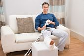 stock photo of crutch  - Portrait Of A Smiling Man Sitting On Sofa With Crutches At Home - JPG