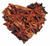 stock photo of cinnamon sticks  - Star anise cinnamon sticks and cloves in the form of heart on a white background - JPG
