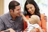 picture of hispanic  - Hispanic couple at home with baby - JPG