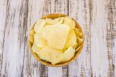 pic of potato chips  - Potato chips in wooden bowl on white wooden table background - JPG