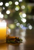 picture of bundle  - Bundle of cinnamon wrapped in ribbon on a wooden table with a burning candle - JPG