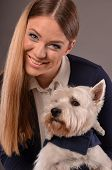 foto of westie  - Young smiling blonde girl and her pet West Highland Terrier studio shot grey background - JPG